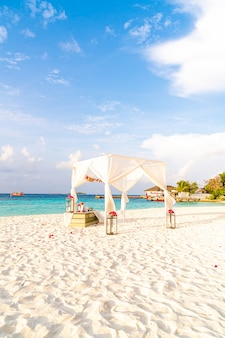 Huwelijksboog op strand met tropische resort maldiven en zee