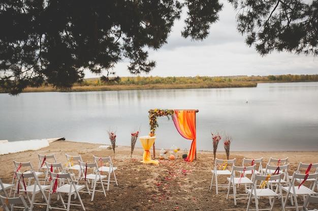 Huwelijksboog van bloemen en stof op het zandstrand. bruiloft decor