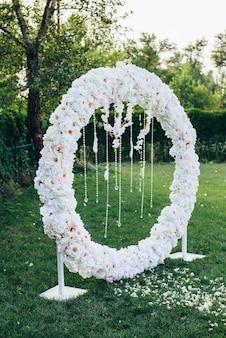 Huwelijksboog van witte bloemen van een ronde vorm versierd met kralen en veren op een achtergrond van de natuur