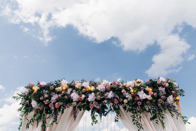 Huwelijksboog versierd met bloemen en gloeilampen