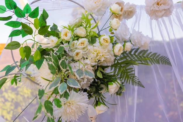 Huwelijksboog versierd met doek en bloemen buitenshuis. mooie bruiloft opgezet.