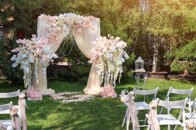 Huwelijksboog versierd met doek en bloemen buitenshuis