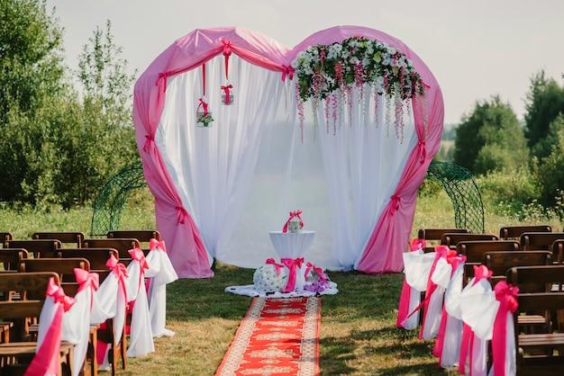 Huwelijksboog voor ceremonie versierd met witte en roze stof en bloemen