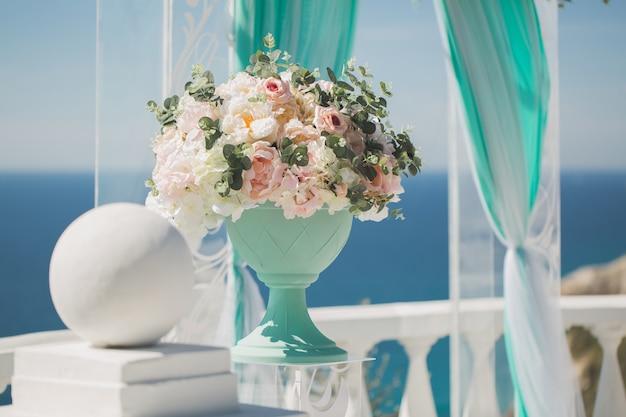 Huwelijksboog voor de ceremonie en een vaas met bruiloft bloemen