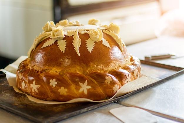 Huwelijksbrood op ovendienblad. gebakken product met decoratie. tradities van het vaderland. nodig gasten uit voor de vakantie.