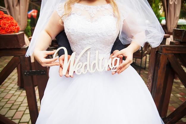 Huwelijksbruid die een teken uitstekende kleur houden