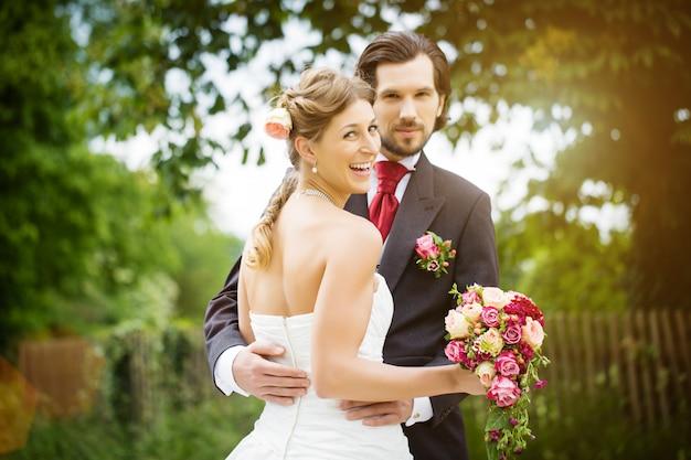 Huwelijksbruid en bruidegom in een weide, met bruids boeket