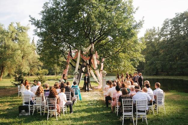 Huwelijksceremonie buiten bruidegom en bruid die zich door de grote boomdecoratie in het park bevinden