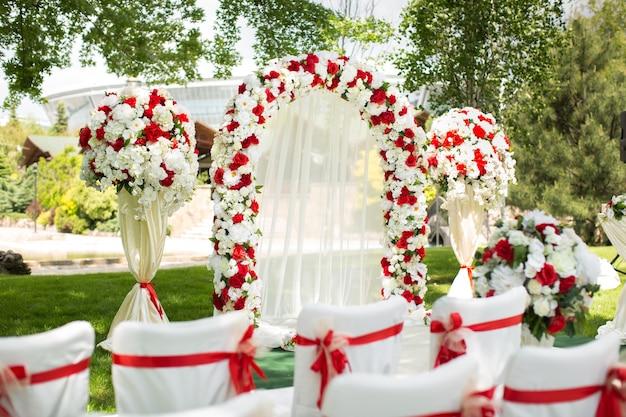 Huwelijksceremonie buitenshuis. huwelijksboog versierd met rode bloemen.