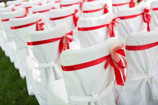Huwelijksceremonie buitenshuis. witte stoelen met rood lint.
