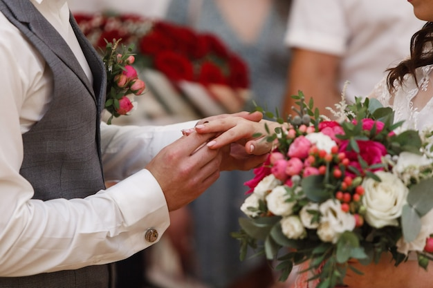 Huwelijksceremonie close-up. jonggehuwden ruilen de gouden trouwringen. net getrouwd stel. hij zette trouwring voor haar. bruidegom zet ring voor bruid