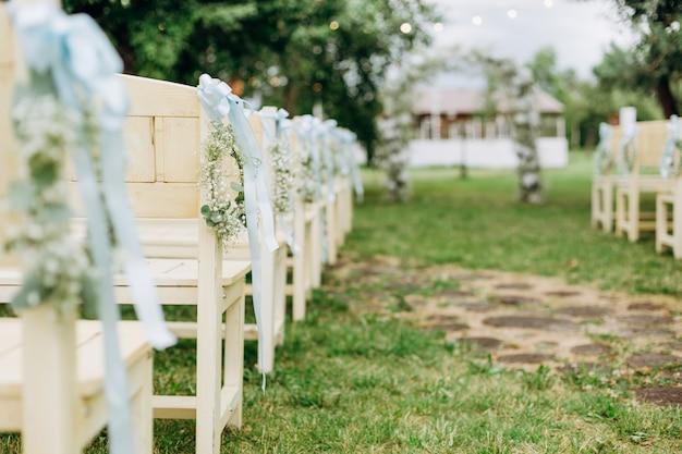 Huwelijksceremonie decor witte stoel bloemen