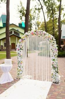 Huwelijksceremonie decoratie. witte boog met bloemen concept. detailopname.