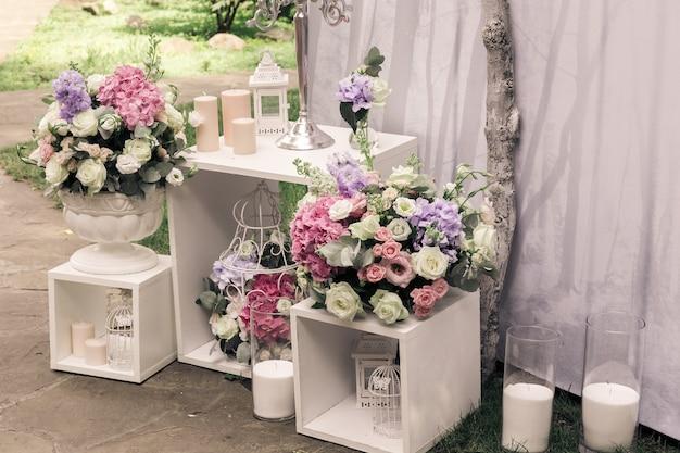 Huwelijksceremonie decoraties boeketten van bloemen / kaarsen in restaurant buitenshuis.