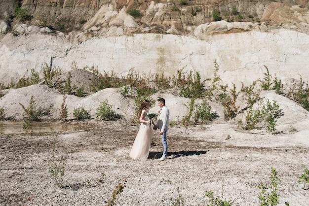 Huwelijksceremonie in de bergen. de bruid en bruidegom staan voor de zanderige bergen. het gelukkige paar, een prachtige bruiloft op een schilderachtige locatie