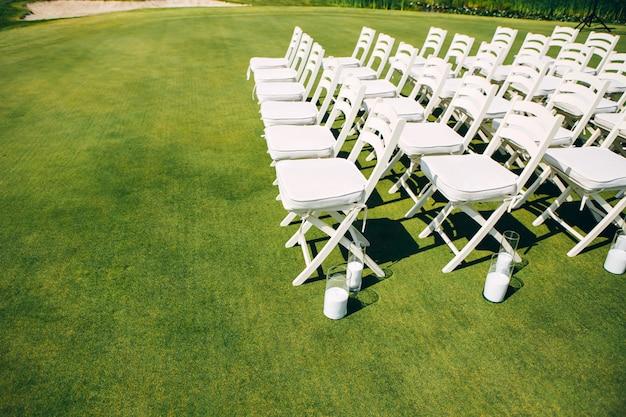 Huwelijksceremonie in de natuur. rijen met witte stoelen op het gazon.