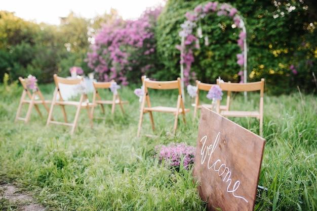 Huwelijksceremonie in het bos tussen de bomen op het groene gras