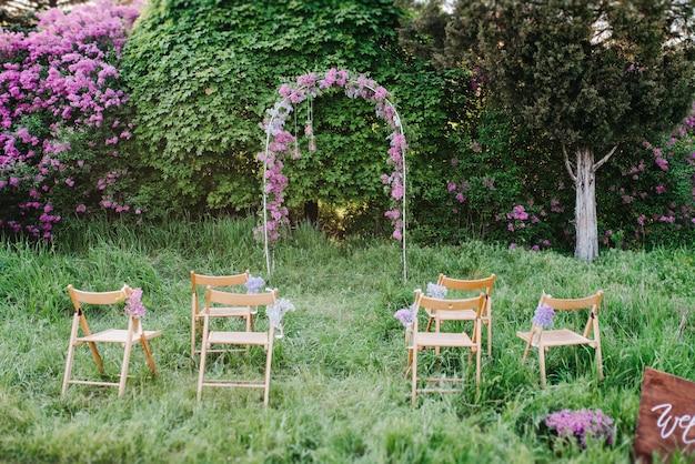 Huwelijksceremonie in het bos tussen de bomen op het groene gras Premium Foto