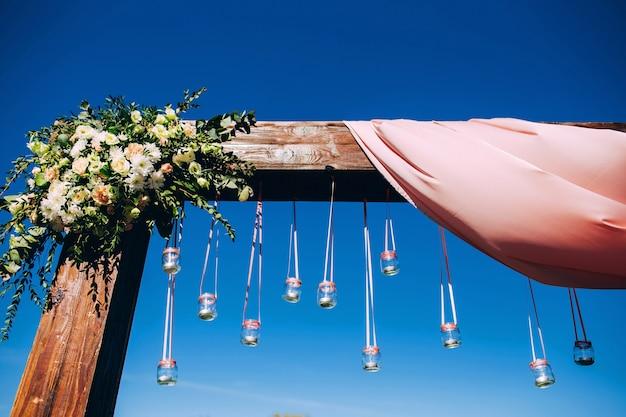 Huwelijksceremonie op het meer. bruiloft decor roze. houten terras. rustiek decor.