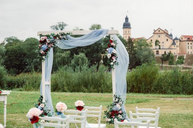 Huwelijksceremonie op straat op het groene gazon.decoratie met bogen van verse bloemen voor de ceremonie.