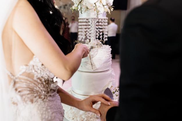 Huwelijksceremonie van cakeknipsel met bruidegom en bruid