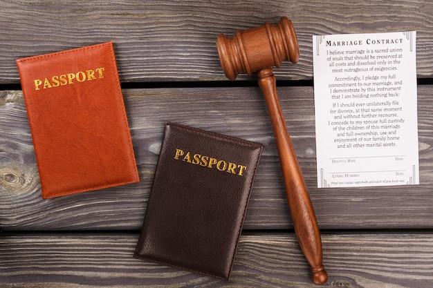 Huwelijkscontract concept. paspoorten met hamer op hout.