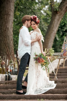 Huwelijksdecoratie in de stijl van boho, bloemstuk, gedecoreerde tafel in de tuin.