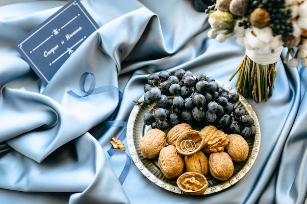 Huwelijksdecoratie met druiven en noten in een plaat op blauwe doekachtergrond, hoge hoekmening.