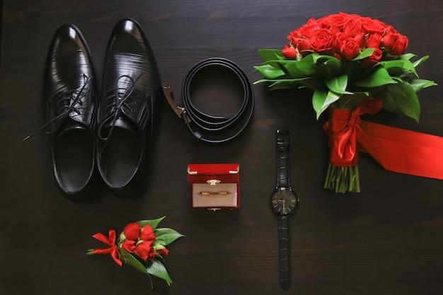 Huwelijksdetails. bruidegom accessoires. schoenen, ringen, riem, corsages en horloge op tafel.