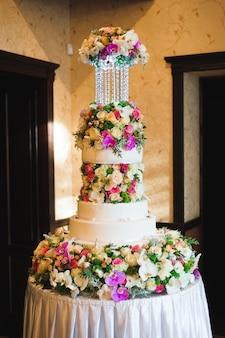 Huwelijksdetails - bruidstaartdessert met bloemen als decor