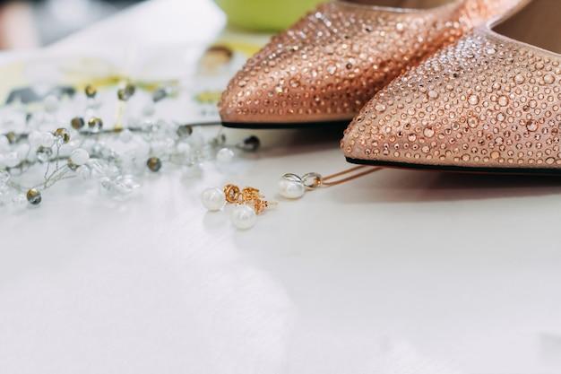 Huwelijksdetails. schoenen, oorbellen, hanger en hoofdsieraden in de buurt