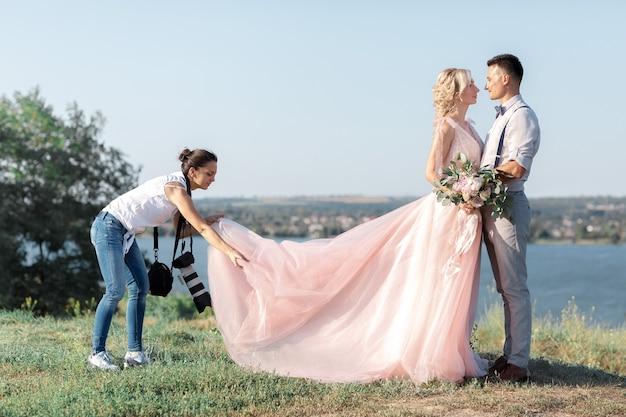 Huwelijksfotograaf maakt foto's van bruid en bruidegom in de natuur. bruidspaar op fotoshoot. fotograaf in actie