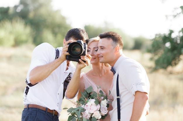 Huwelijksfotograaf maakt foto's van bruid en bruidegom in de natuur. fotograaf toont net gemaakte foto's aan bruidspaar