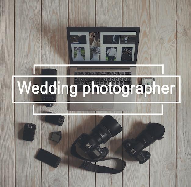 Huwelijksfotograaf uitrustingsstukken plat leggen. bovenaanzicht op fotocamera's met apparatuur, smartphone, bundel geld en laptop met trouwfoto's