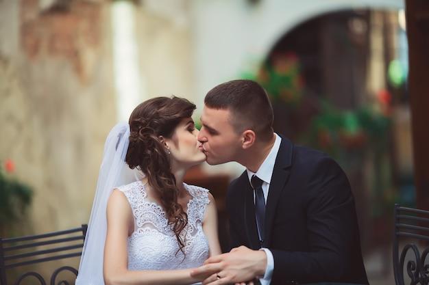 Huwelijksfotografie. bruid en bruidegom zitten in een cafe, omhelzen en glimlachen.