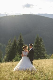 Huwelijksfotografie in de bergen. de bruidegom omhelst de bruid. pasgetrouwden kijken elkaar in de ogen.