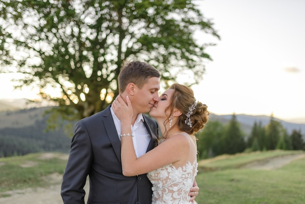 Huwelijksfotografie in de bergen. de pasgetrouwden kussen. detailopname.