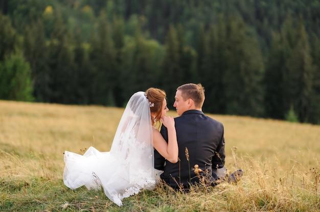 Huwelijksfotografie in de bergen. pasgetrouwden zitten met hun rug op het gras en kijken elkaar aan.