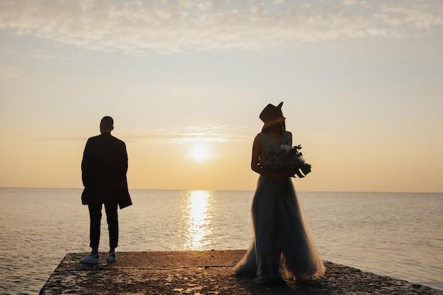 Huwelijksfotosessie van een stijlvol stel aan de kust. blauwe trouwjurk op de bruid.