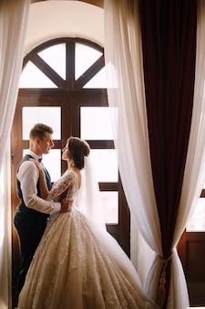 Huwelijksfotoshoot in montenegro perast staat een bruidspaar bij het houten raam