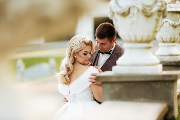Huwelijksfotoshoot mooie paarbruid en bruidegom lange sluier en witte kleding op bergen achtergrondmeerceremonie luxe mooie zonnige dag