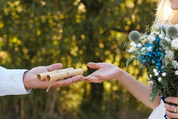 Huwelijksgeloften op opgerold vel papier op de palm van de bruidegom, bruidsboeket, rustiek buitenhuwelijksconcept.