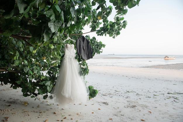 Huwelijkskleding birde en bruidegom op bomen in het strand