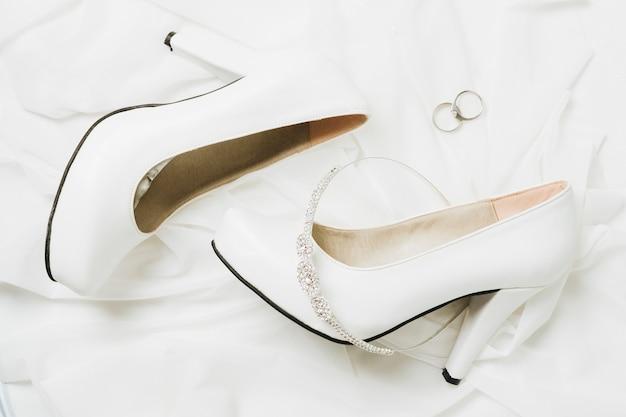 Huwelijkskroon en ringen met huwelijks hoge hielen op witte sjaal