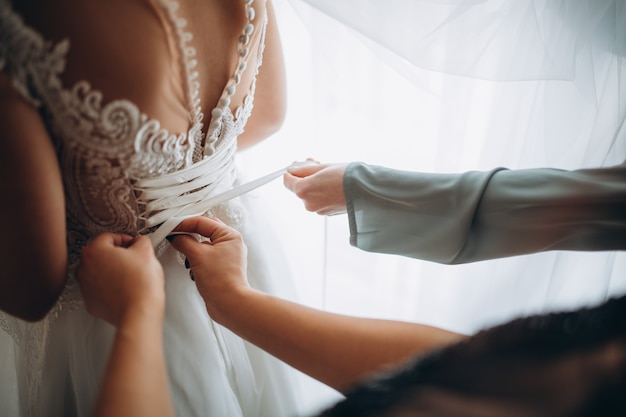 Huwelijksochtend. zijaanzicht van de bruid in trouwjurk. bruidsmeisjes bruid voorbereiden op de huwelijksdag.