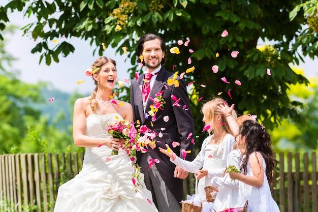 Huwelijkspaar en bruidsmeisje die bloemen overgieten