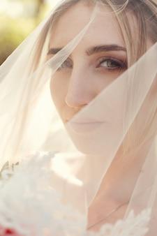 Huwelijksportret van een vrouwenbruid onder een witte sluier. een meisje in een trouwjurk met een boeket bloemen in haar handen