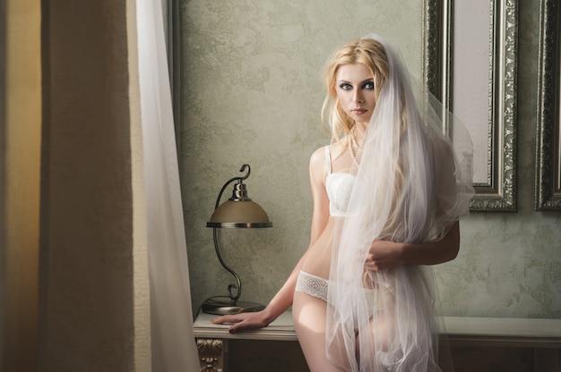 Huwelijksportret van jonge mooie blondebruid met krullend haar