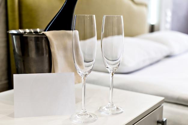 Huwelijksreis concept. champagne-emmer dichtbij bed in een hotelkamer