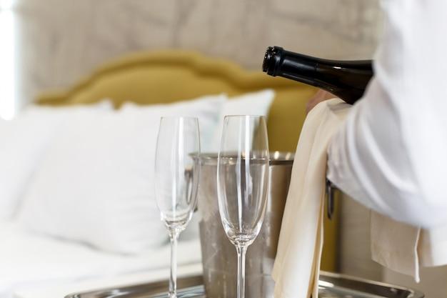 Huwelijksreis concept. champagne-emmer dichtbij bed in een hotelruimte